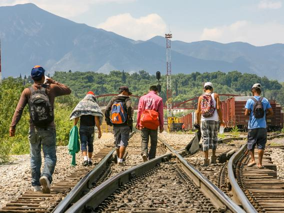 A group of Central American migrants walking along a train track.